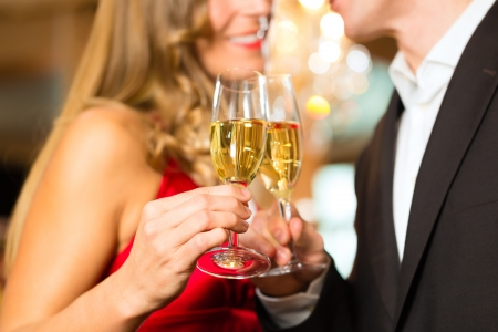 clinking: Couple, man and woman, drinking champagne in a fine dining restaurant, each with glass of sparkling wine in hand Stock Photo