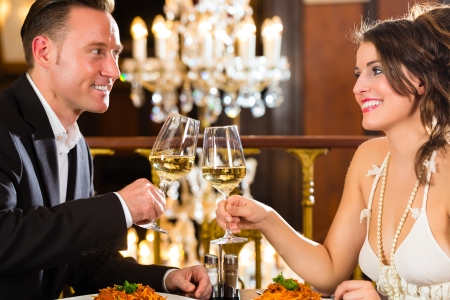 dinner date: happy couple have a romantic date in a fine dining restaurant they drink wine and clinking glasses, cheers - a large chandelier is in Background