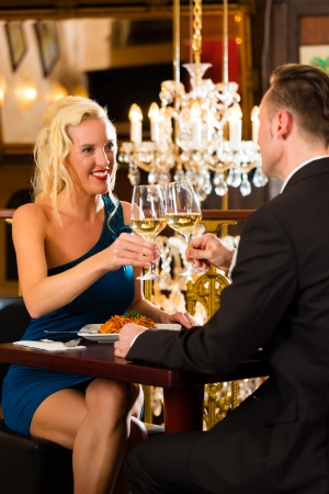 happy couple have a romantic date in a fine dining restaurant they drink wine and clinking glasses, cheers - a large chandelier is in Background photo