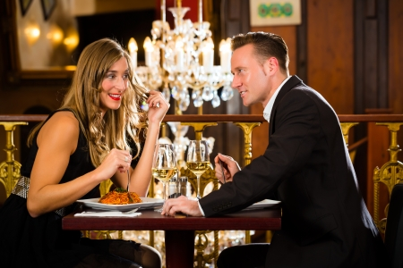 fine dining: happy couple have a romantic date in a fine dining restaurant they drink wine and clinking glasses, cheers - a large chandelier is in Background