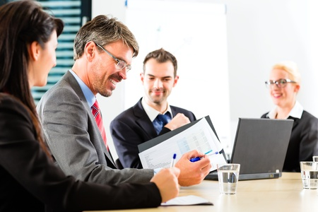 Business - businesspeople have a meeting with presentation in office, they negotiate a contract Stock Photo - 19942131