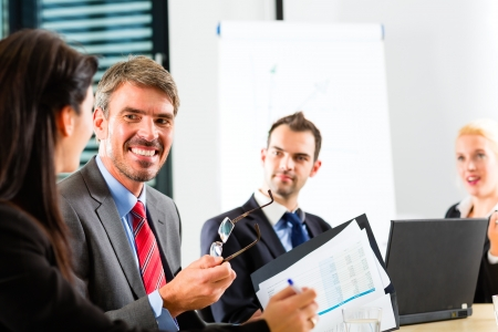 Business - businesspeople have a meeting with presentation in office, they negotiate a contract photo