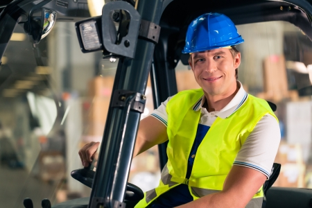 forklift driver in protective vest and forklift at warehouse of freight forwarding company, smiling photo