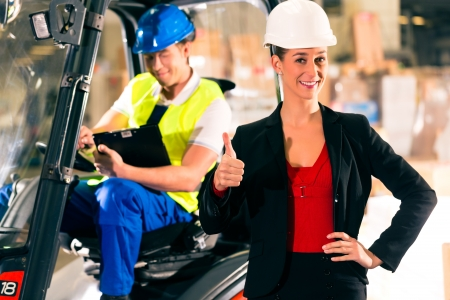 Forklift driver and female super visor with clipboard at warehouse of freight forwarding company - thumbs up Stock Photo - 19942194