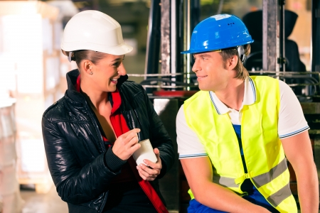 Forklift driver and female coworker takes a break at warehouse of freight forwarding company photo