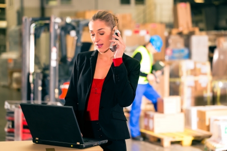 fast delivery: Friendly Woman, dispatcher or supervisor using cell phone and laptop at warehouse of forwarding company, smiling, a forklift is in Background