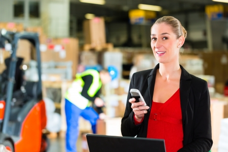 dispatcher: Friendly Woman, dispatcher or supervisor using cell phone and laptop at warehouse of forwarding company, smiling, a forklift is in Background
