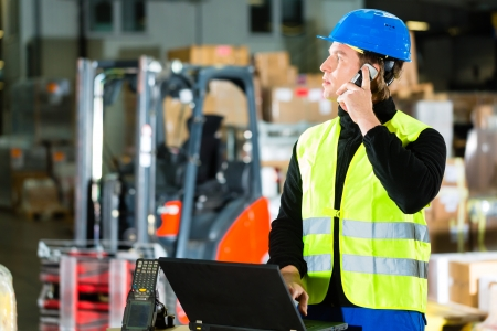 carretillas almacen: Almacenero con chaleco antibalas, un escáner y un ordenador portátil en el almacén de la compañía de transporte de carga con un teléfono móvil
