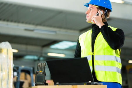 Warehouseman with protective vest, scanner and laptop in warehouse at freight forwarding company using a mobile phone photo