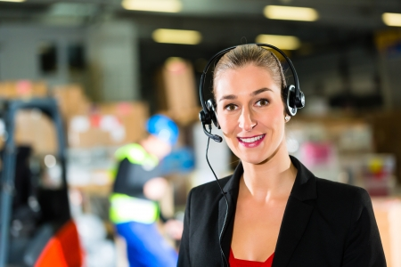 Friendly Woman, dispatcher or supervisor using headset at warehouse of forwarding company, smiling photo