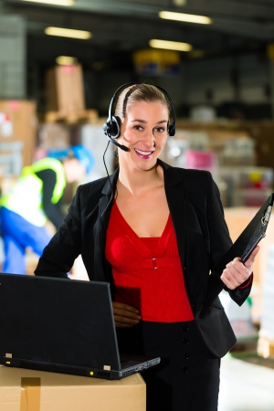 Friendly Woman, dispatcher or supervisor using headset and laptop at warehouse of forwarding company, smiling Stock Photo - 19942195