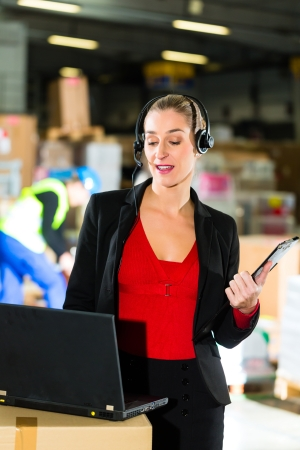 Friendly Woman, dispatcher or supervisor using headset and laptop at warehouse of forwarding company, smiling photo