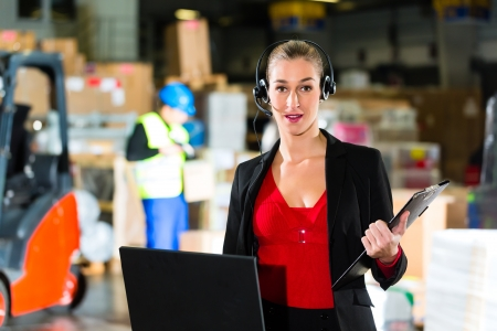 mobile headsets: Friendly Woman, dispatcher or supervisor using headset and laptop at warehouse of forwarding company, smiling