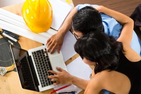 freiberufler: Freelancer - Architekt arbeitet zu Hause auf einem Design oder Entwurf auf seinem Schreibtisch sind B?cher, ein Laptop und ein Helm oder harten Hut