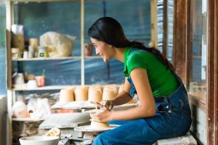 alfarero: Mujer Potter creaci�n de un taz�n de fuente en una rueda de alfareros