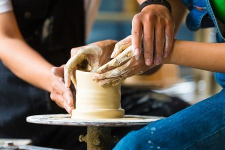 alfarero: Mujer Potter creaci�n de un taz�n de fuente en una rueda de alfareros, el maestro alfarero ayud�ndola