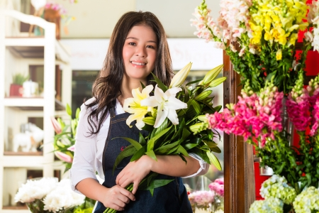 seller: Friendly Asian florist or Saleswoman in a flower shop, holding a flower bouquet