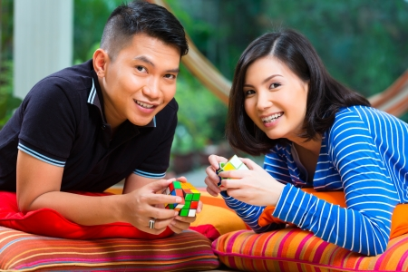 Young Indonesian couple - man and woman - at home playing with a magic cube photo