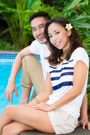 Young Indonesian couple - man and woman - sitting in the garden on swimming pool in tropical environment photo