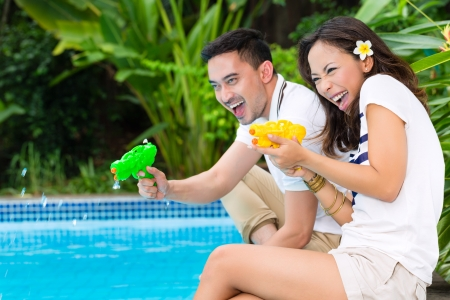Young Indonesian couple - man and woman - in the garden on swimming pool in tropical environment, thy playing with water pistols