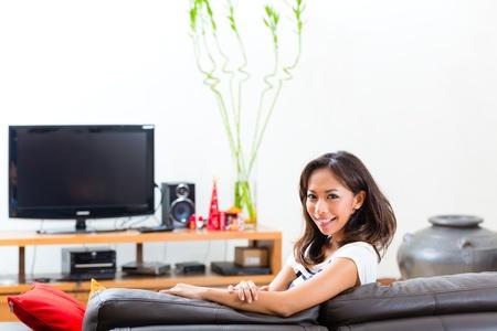 indonesian woman: Joven mujer indonesia que se sienta en el sof� de la sala de estar Foto de archivo