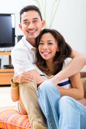 Young Indonesian couple - man and woman - sitting at home on the floor, its weekend and they enjoying the leisure time photo
