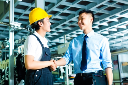 Worker or production manager and owner, ceo or controller shake hands in a factory photo