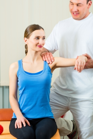 masaje deportivo: Paciente femenino en la fisioterapia haciendo ejercicios físicos con su terapeuta, que le da un masaje médico