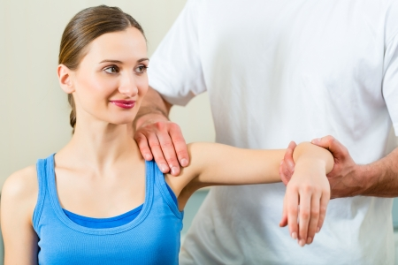 rehabilitation: Female Patient at the physiotherapy doing physical exercises with her therapist, he gives her a medical massage