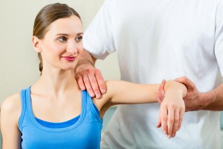fysiotherapie: Vrouwelijke Patiënt bij de fysiotherapie die fysieke oefeningen doet met haar therapeut, geeft hij haar een medische massage