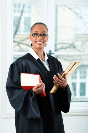 Young female lawyer working in her office with a typical law book and a file or dossier photo