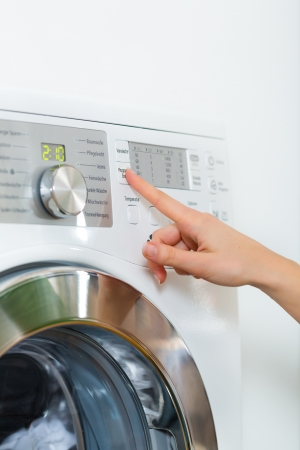 clothes washing: Joven ama de casa o tiene una lavander?a en el d?a en casa, seleccione el programa