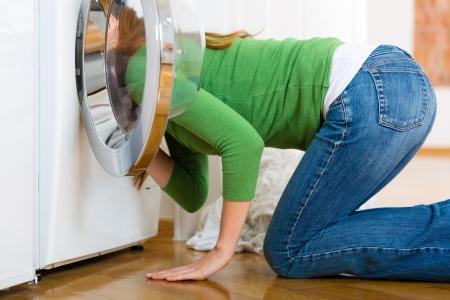 lavando ropa: Joven ama de casa o tiene una lavander�a en el d�a en su casa, ella es la b�squeda de los calcetines perdidos