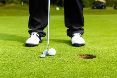 golf: Golf player putting ball into hole, only feet and iron to be seen
