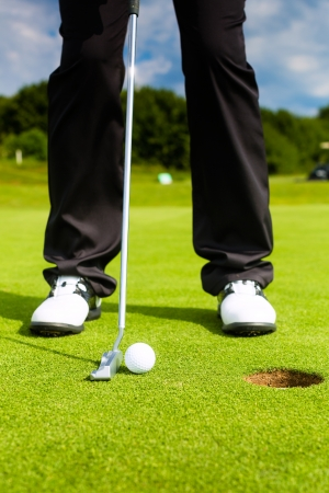 Golf player putting ball into hole, only feet and iron to be seen photo