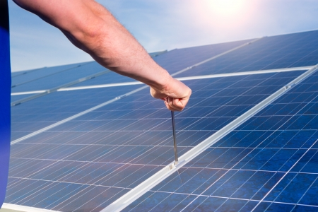 Photovoltaic system with solar panels for the production of renewable energy through solar energy, a technician using a screwdriver or tool photo