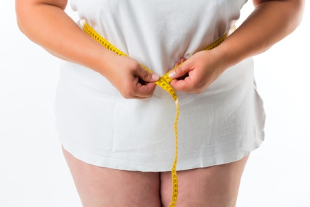 loose skin: obese woman measuring her waist with tape