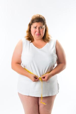 persona triste: mujer obesa que mide su cintura con una cinta y no es feliz
