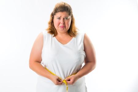 obesidad: mujer obesa que mide su cintura con una cinta y no es feliz