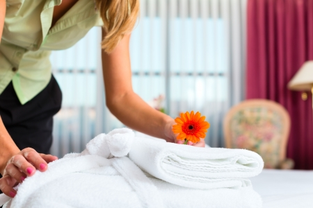 accommodation: Maid doing room service in hotel, she is making up the beds Stock Photo