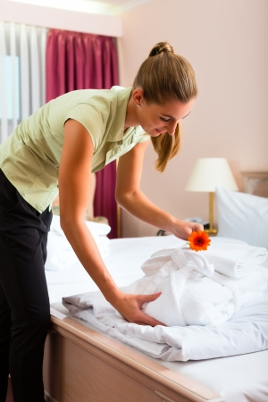 room service: Maid doing room service in hotel, she is making up the beds Stock Photo