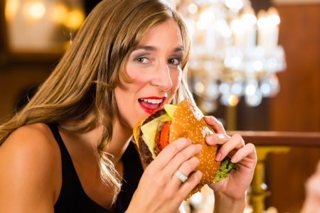 etiquette: Young woman in a fine dining restaurant eat a hamburger, she behaves improperly