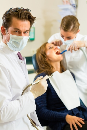 Dentists in his surgery holds a drill and looking at the viewer, in the background his assistant is giving a female patient a treatment photo