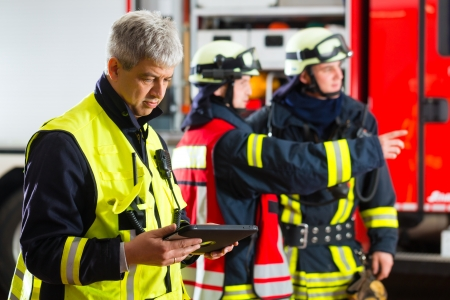 bombero de rojo: Bomberos - líder de escuadrón, utilizó la computadora de la tableta de planificar el despliegue y mirando al espectador