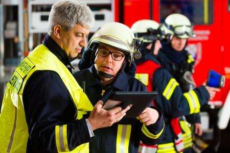 bombero de rojo: Bomberos - Squad l?r da instrucciones, utiliz? Tablet PC para planificar el despliegue