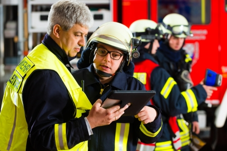 emergency plan: Fire brigade - Squad leader gives instructions, he used the Tablet Computer to plan the deployment Stock Photo