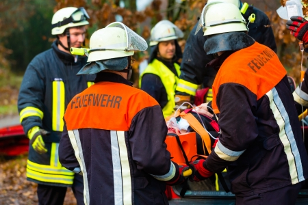 emergency cart: Accident - Fire brigade and Rescue team pulling cart with wounded person wearing a neck brace and respirator Stock Photo