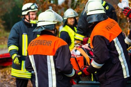 paciente en camilla: Accidente - Cuerpo de Bomberos y Rescate de equipo tirando de carro con persona herida que llevaba un cuello ortop?dico y un respirador,