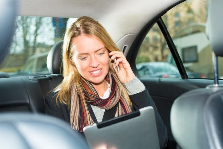 taxis: Young businesswoman driving in taxi, she using tablet computer and is on the mobile phone Stock Photo