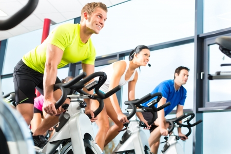 spin: Young People - group of women and men - doing sport Spinning in the gym for fitness